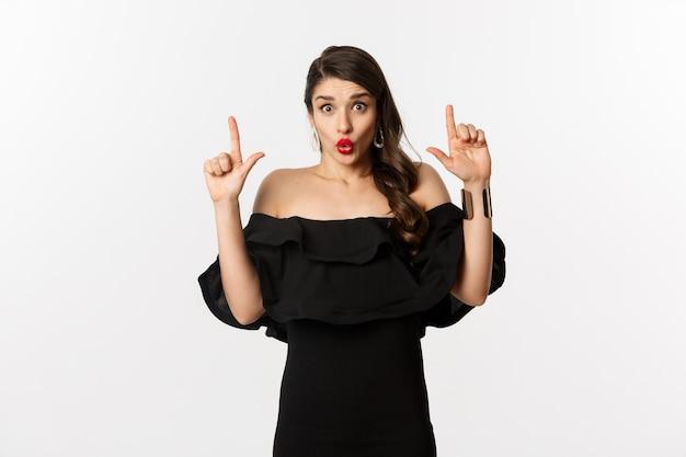 Mode en schoonheid. verraste vrouw die advertentie bovenaan toont, vingers omhoog wijst en wow verbaasd zegt, staande op een witte achtergrond.