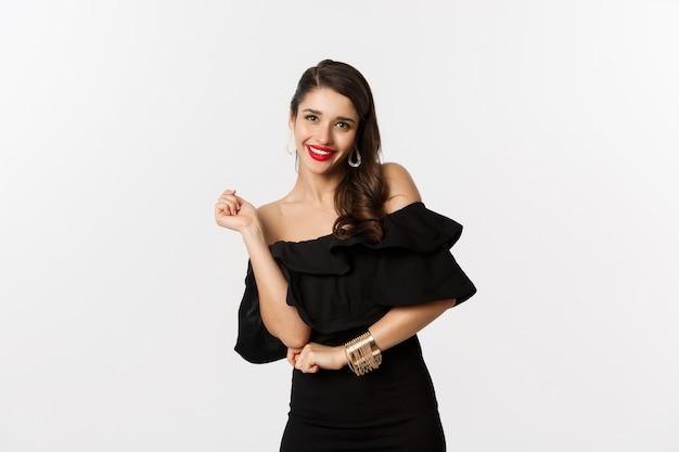 Mode en schoonheid. vrouw vieren en dansen in zwarte jurk, plezier maken en glimlachen, staande op een witte achtergrond.