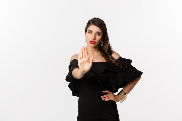 Mode en schoonheid. zelfverzekerde aantrekkelijke vrouw die nee zegt, stopgebaar toont en serieus naar de camera kijkt, afkeurt en verbiedt, staande op een witte achtergrond.
