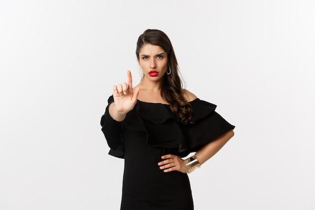 Mode en schoonheid. zelfverzekerde en serieuze dame in zwarte jurk, vinger in stopgebaar tonen, iets verbieden en afkeuren, staande op een witte achtergrond.