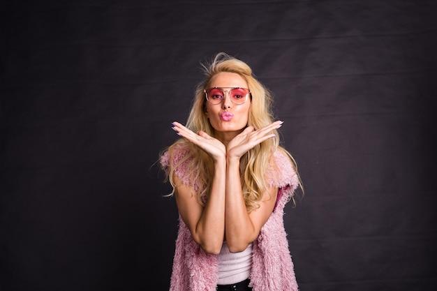 Mode- en schoonheidsconcept - mooi blond model verzendt kusjes over donker oppervlak