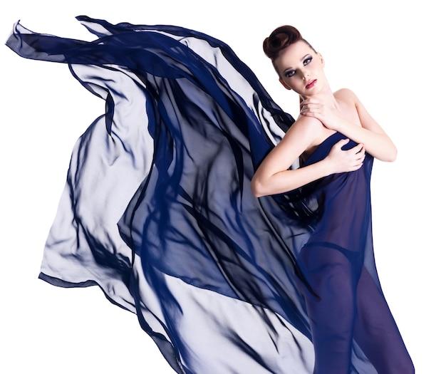 Mode en stijlbeeld van mooie glamourvrouw in blauwe chiffon die op wit wordt geïsoleerd