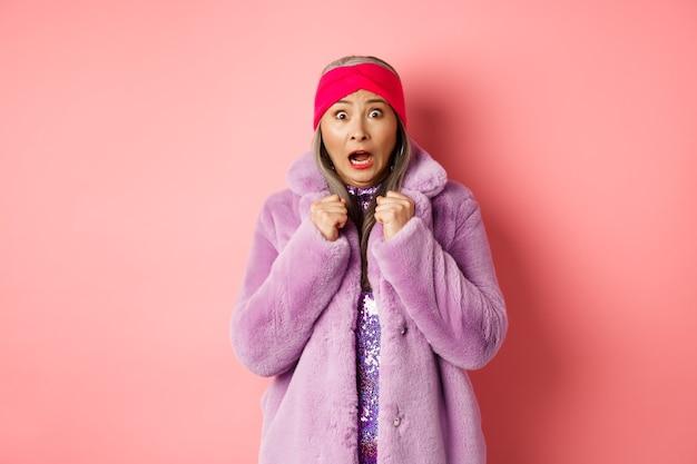 Mode en winkelconcept. bange oudere vrouw schreeuwt en staart geschrokken naar de camera, springt van angst, draagt paarse winterjas en hoofdband, roze achtergrond