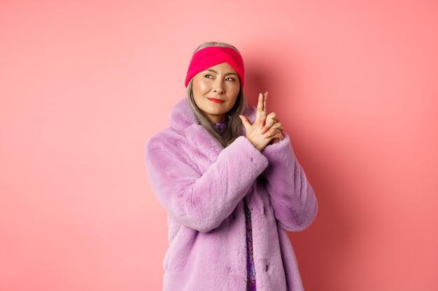 Mode en winkelconcept. coole en stijlvolle aziatische senior dame in paarse nepbontjas, vingergebaar maken en naar links kijken met brutale glimlach, handelend als geheimagent, roze achtergrond