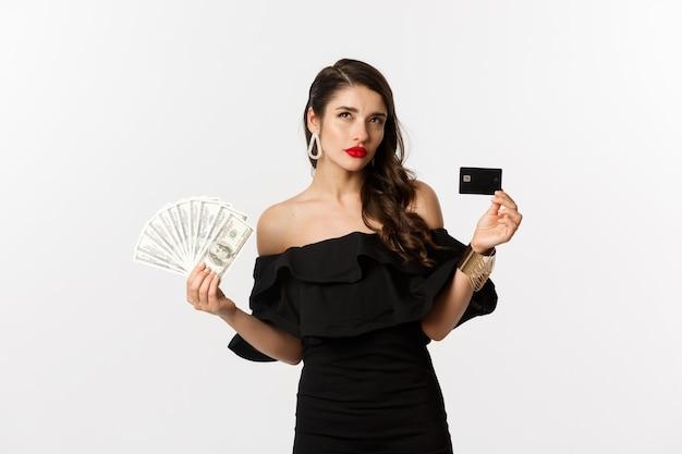 Mode en winkelconcept. doordachte vrouw met creditcard en dollars, denken en opzoeken, witte achtergrond