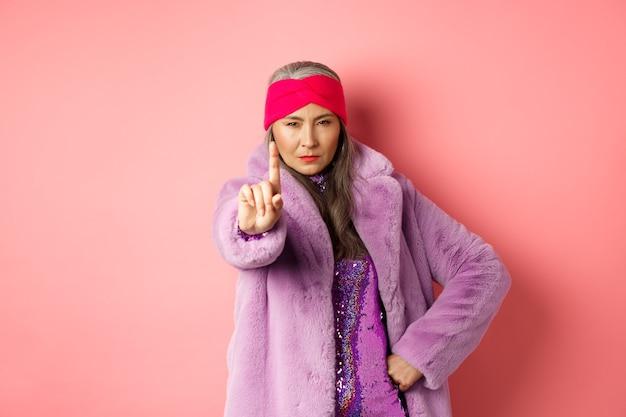 Mode en winkelconcept. ernstige aziatische senior vrouw die niet zo snel gebaar toont, uitgestrekte vinger schudt om te stoppen of je te waarschuwen, vastberaden naar de camera kijkt, stijlvolle paarse kleding draagt