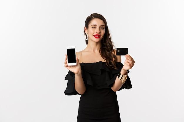 Mode en winkelconcept. mooie vrouw met rode lippen, knipogend naar camera, smartphonescherm en creditcard tonend, online kopend, witte achtergrond