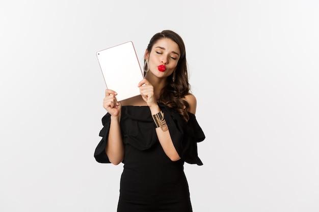 Mode en winkelconcept. mooie vrouw met rode lippen, zwarte jurk dragen, digitale tablet tonen en kussen gezicht maken, witte achtergrond