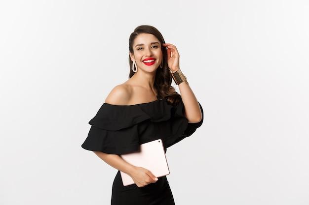 Mode en winkelconcept. stijlvolle jonge vrouw met glamour make-up, zwarte jurk dragen, digitale tablet houden en glimlachen, witte achtergrond.