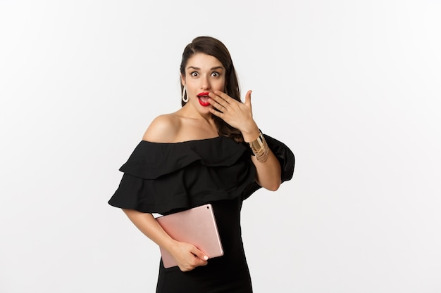 Mode- en winkelconcept. stijlvolle jonge vrouw met glamour make-up, zwarte jurk dragen, digitale tablet vasthouden en op zoek verrast, witte achtergrond.