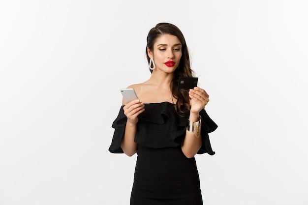 Mode- en winkelconcept. vrouw in make-up en zwarte jurk online bestellen, betalen met creditcard en mobiele telefoon, witte achtergrond.