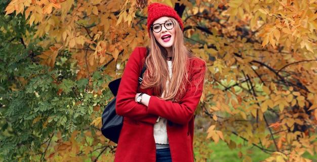 Mode foto van blonde vrouw met lange haren wandelen in zonnige herfst park in trendy casual outfit.
