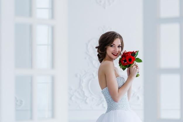 Mode foto van een mooie bruid met bloemen boeket in haar handen in de lichte kamer naast de deuren