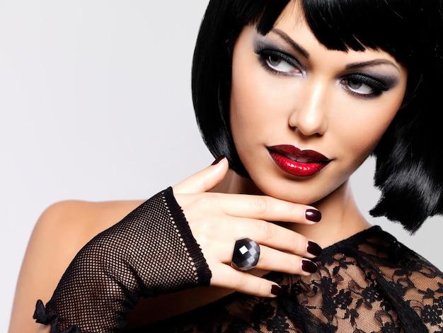 Mode foto van een mooie brunette vrouw met geschoten kapsel. het gezicht van het close-upmeisje met rode lippen en spijkers