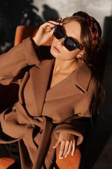 Mode foto van een mooie jonge vrouw in trendy zonnebril en jas in een fauteuil in het interieur. model meisje in lente outfit poseren in interieur. levensstijl in de stad. vrouwelijke mode. close-up portret