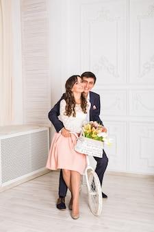 Mode foto van elegante verliefde paar poseren in studio met klassiek interieur in de buurt van de fiets