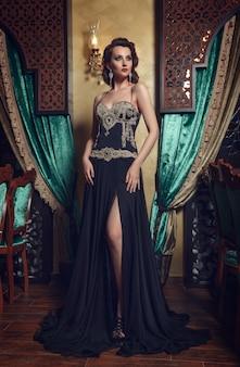 Mode foto van jonge prachtige vrouw in zwarte jurk.