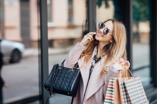 Mode foto van jonge stijlvolle blonde vrouw die op straat loopt, trendy outfit draagt, boodschappentassen vasthoudt en telefonisch spreekt.