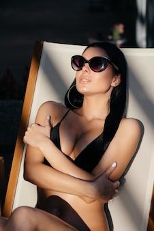 Mode foto van mooie gebruinde vrouw met zonnebril in elegante zwarte bikini ontspannen naast een zwembad op houten rieten stoel