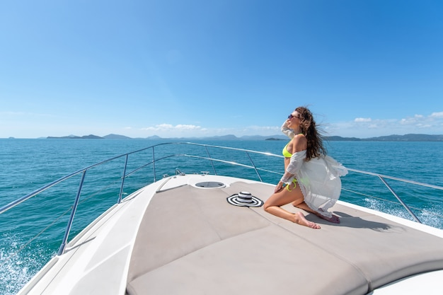 Mode foto van schattige jonge vrouw zittend op de rand van luxe jacht en op zoek naar de zee tijdens zeiltocht. gelukkige vrouw genieten van zomer reizen. vakantie concept