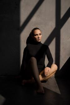 Mode foto van sensuele vrouw ze zit op de grond naast het raam een schaduw op haar