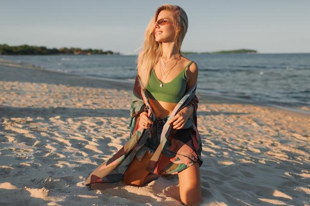 Mode foto van sexy blonde vrouw in groene crop top en jeans poseren op tropisch strand.