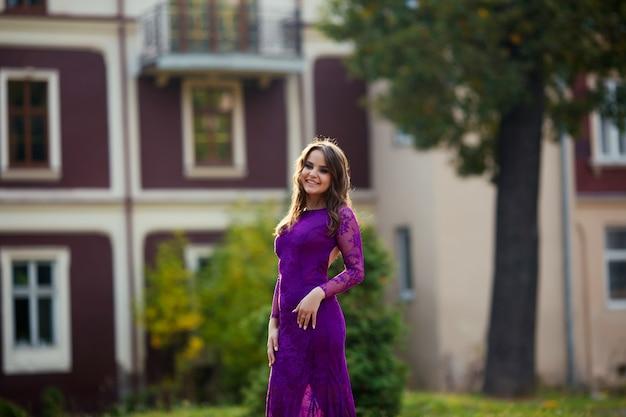 Mode foto van sexy glamour model met lang donker haar in een elegante zwarte jurk poseren in het park glimlachen