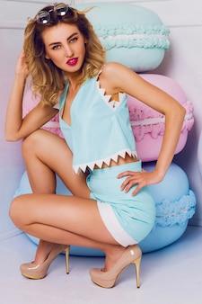Mode foto van sexy mooie vrouw met blond kapsel dragen trendy blauw lederen top en korte broek zitten in de buurt van grote kleurrijke rekwisieten snoep. moderne jonge modieuze dame in pastelkleuren.