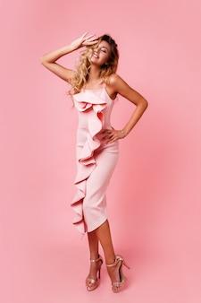 Mode foto van volledige hoogte van blonde vrouw met perfecte golvende kapsel in roze feestjurk poseren. hoge hakken. verras gezicht. ruimte voor tekst.