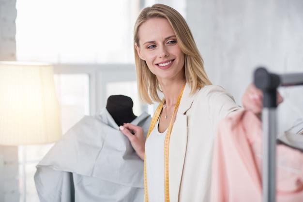 Mode gebied. vrolijke, vrolijke zakenvrouw die zich uitstrekt voor kledingstuk tijdens het glimlachen