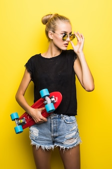 Mode gelukkig lachend hipster cool meisje in zonnebril en kleurrijke kleding met skateboard plezier buitenshuis tegen de oranje achtergrond