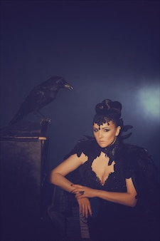 Mode gotisch portret van een mooie brunette met raaf in een lange zwarte jurk gemaakt van raafveren. halloween