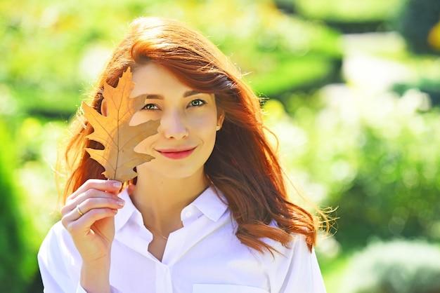Mode herfst jonge vrouw houdt gele esdoorn bladeren op herfst park achtergrond