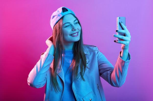 Mode hipster cool meisje dat zelfportret op slimme telefoon neemt terwijl poseren geïsoleerd over roze neon ruimte