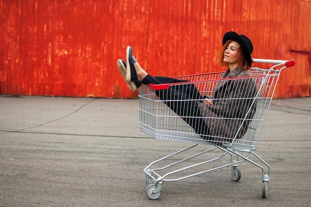Mode hipster cool meisje in winkelwagen met plezier tegen de kleurrijke oranje muur.