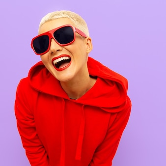 Mode hipster glimlachend model in rode sweater en zonnebril straat stedelijke stijl