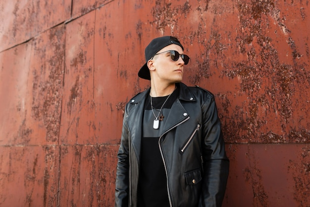 Mode hipster man met zonnebril in mode-outfit met leren jas en pet in de buurt van rustieke metalen muur