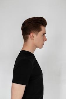 Mode hipster man model met kapsel in zwarte t-shirts in studio op een grijze achtergrond
