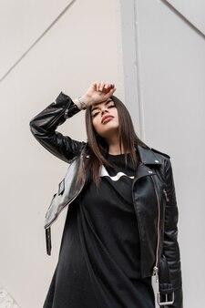 Mode hipster meisje in modieuze lederen rock kleding met jas en sweatshirt poseert in de buurt van de grijze muur in de stad en kijkt naar de camera