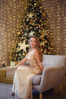 Mode interieur foto van mooie sensuele vrouw met blond haar in luxe gouden jurk poseren naast een kerstboom. wens je een vrolijk kerstfeest.