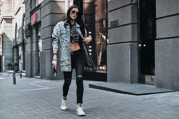 Mode is haar leven. volledige lengte van jonge aantrekkelijke vrouw die haar spijkerjasje aanpast