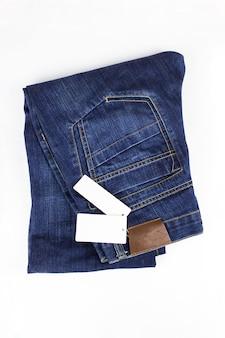 Mode jeans knop. blue jeans liggend op een witte achtergrond met prijskaartje. ruimte kopiëren. kleding, online winkelconcepten.