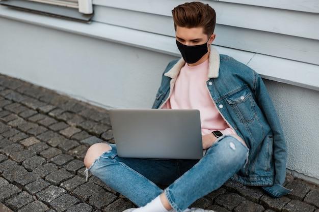Mode jonge freelancer man met zwart medisch masker in stijlvolle denim casual jeans kleding zit met laptop en werkt op afstand aan creatief project. modieuze ontwerper typt buitenshuis op toetsenbord.