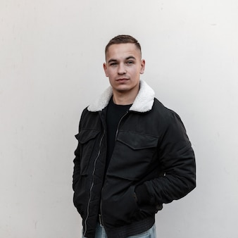 Mode jonge knappe man in stijlvolle zwarte uitloper staat in de buurt van grijze muur