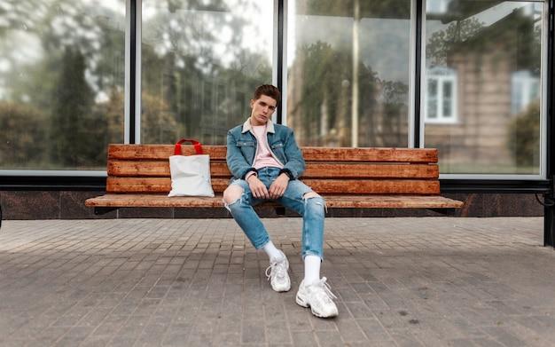 Mode jonge man in modieuze blauwe jeugdjeans kleding in witte stijlvolle sneakers met vintage stoffen tas zit op houten bankje bij bushalte in de stad. stedelijke schattige trendy man in spijkerbroek draagt rust buitenshuis.