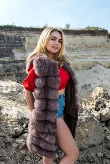 Mode jonge vrouw in bontjas poseren op zand rotsen