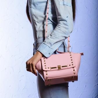 Mode jonge vrouw in spijkerbroek met roze handtas