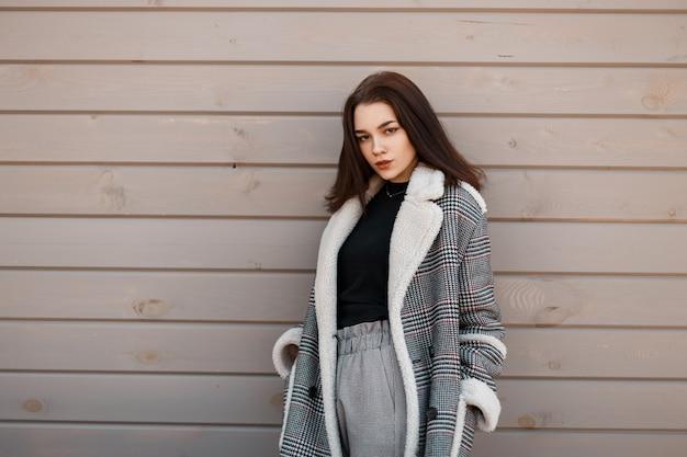 Mode jonge vrouw in stijlvolle uitloper met vintage jas staat netjes op een houten achtergrond