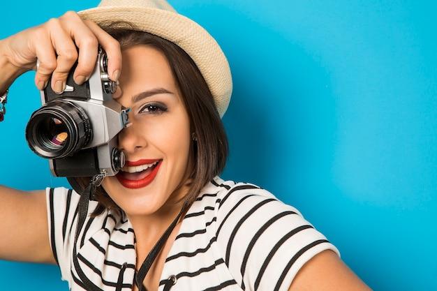 Mode jonge vrouw maakt de foto met oude camera