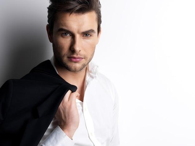 Mode jongeman in wit overhemd houdt de zwarte jas over de muur met contrasterende schaduwen